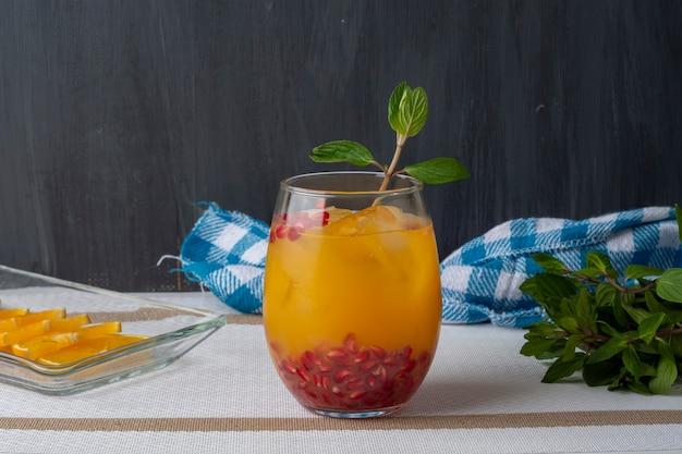 Апельсиновый напиток со льдом граната и мятой в сопровождении тарелки с дольками апельсина