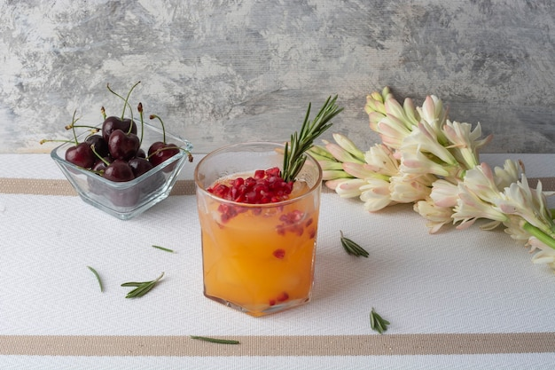 체리와 함께 테이블에 붉은 석류와 로즈마리 가지를 곁들인 오렌지 음료