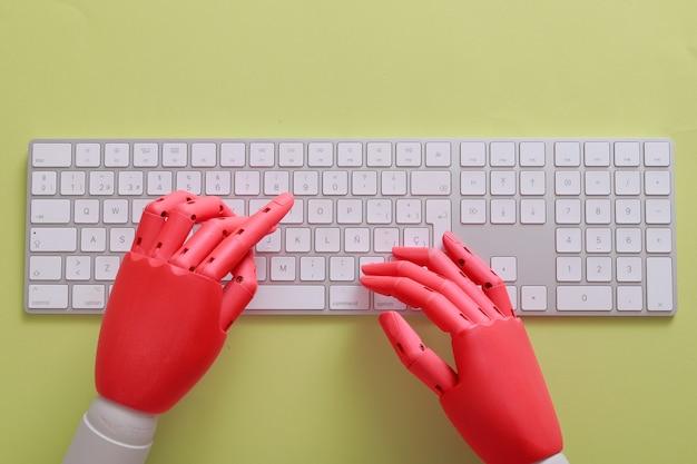 緑の背景を持つキーボードのオレンジ色のダミーの手