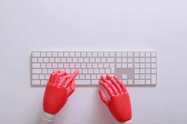 白い背景のキーボードのオレンジ色のダミーの手