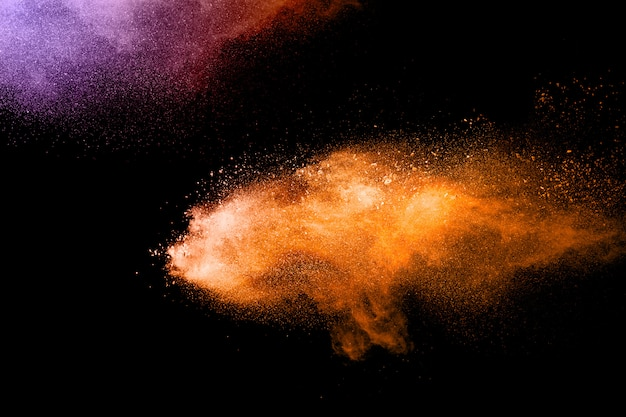 Orange dust particles explosion on white background. powder dust splash.
