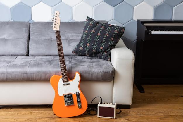 Оранжевая электрогитара и усилитель с кабелем возле кожаного дивана и пианино в гостиной
