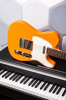 Оранжевая электрогитара лежит на пианино, крупным планом