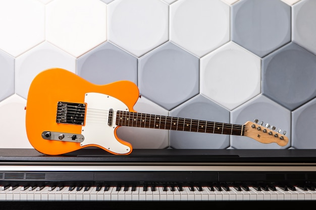 Orange electric guitar laying on piano. concept for music school