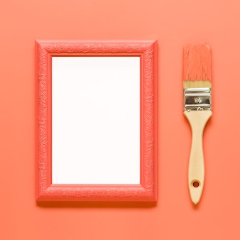 Orange empty frame and wood paintbrush