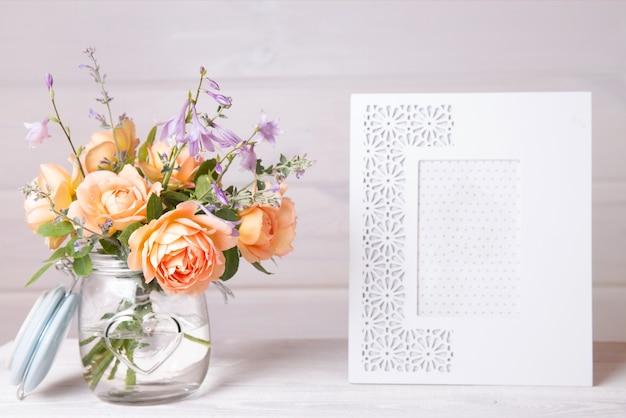 꽃병에 오렌지 영어 장미 꽃입니다. 항아리와 나무 배경에 빈 흰색 사진 프레임. 카피스페이스가 있는 모형.
