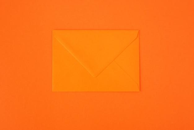 オレンジ色の背景にオレンジ色の封筒