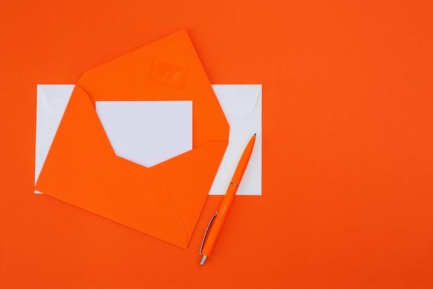 Оранжевый конверт с ручкой на оранжевом фоне. скопируйте пространство. вид сверху. плоская планировка.