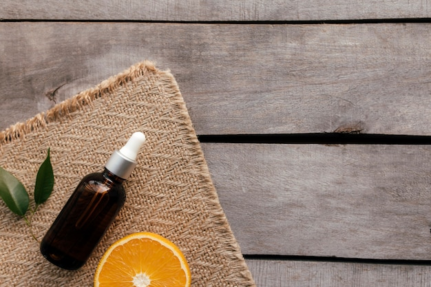 녹색 잎을 가진 유리 병에 오렌지 에센셜 오일. 자루, 고립 된 평면 누워에 나무 배경에 화장품 개념.