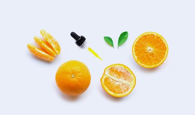 Orange essential oil with dropper on white