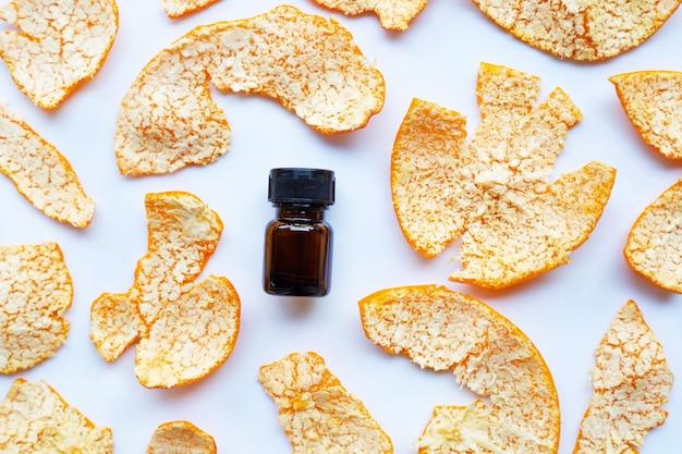 Orange essential oil with orange peel on white background