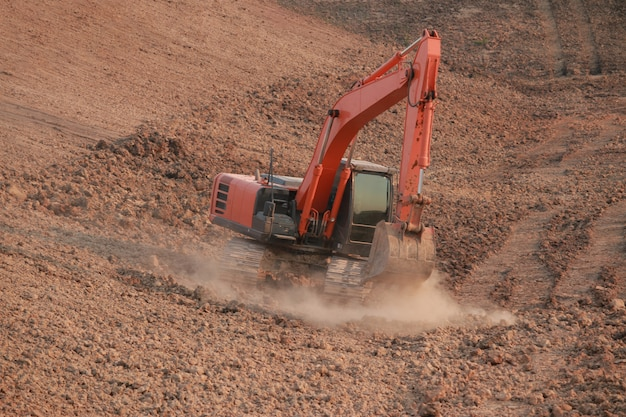 Orange excavator under construction large reservoir, dust by digging the soil.