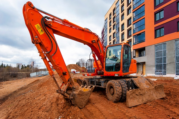 An orange excavator stands next to a multicolored house