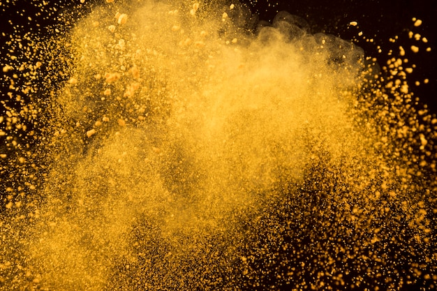 Orange explosion of cosmetic powder on dark background