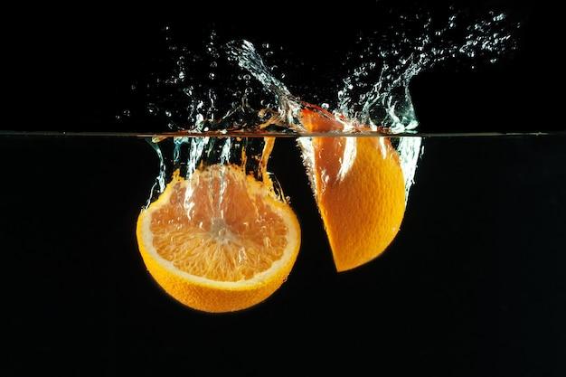 オレンジが水に落ちて水しぶきを作る