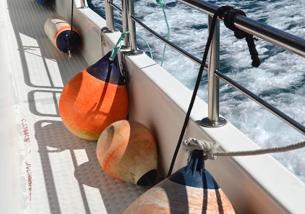 Orange fenders on deck ship going on sea.