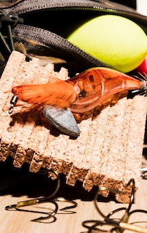 An orange fishing lure with fishing float and corkboard