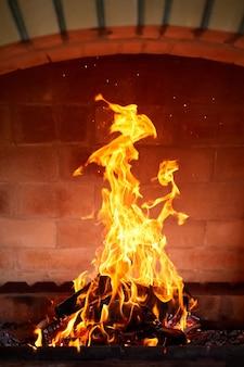 Оранжевое пламя от сжигания дров в кирпичном мангале. крупный план, выборочный фокус
