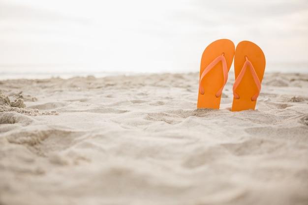 모래에 오렌지 플립 플롭