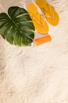 Orange flip flops and monstera leaves on beach
