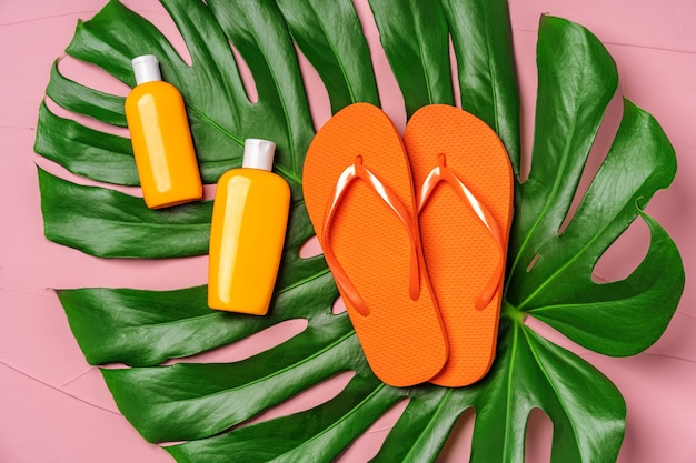 Orange flip-flops with sunscreen creams on big monstera leaf on pink background