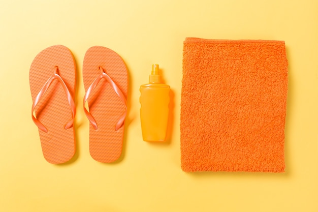 Orange flip flops with towel on yellow background top view flat lay with copy space. holiday vacation travel concept with beach sea accessories.