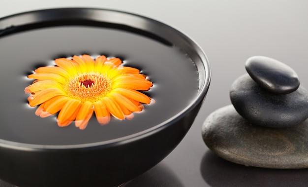 黒いボールと黒い小石のスタックに浮かんでいるオレンジ色の花