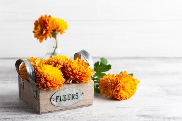 Оранжевые цветы в коробке на деревенском столе