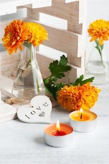 Оранжевые цветы в стеклянном горшке на деревенском столе. открытка с зажженными свечами и сердцем