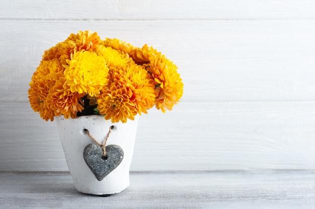 Оранжевые цветы в белом горшке на деревенском столе.