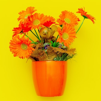 Orange flowers in a pot on a yellow background. vintage. flat lay art