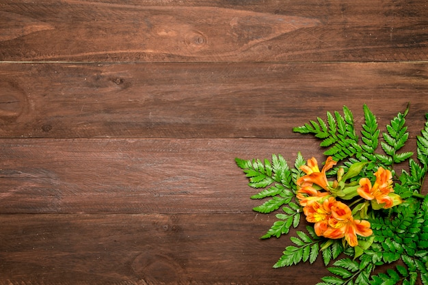 Orange flowers with leaves on wooden background
