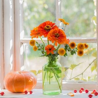 Orange flowers with pumpkin on windowsill