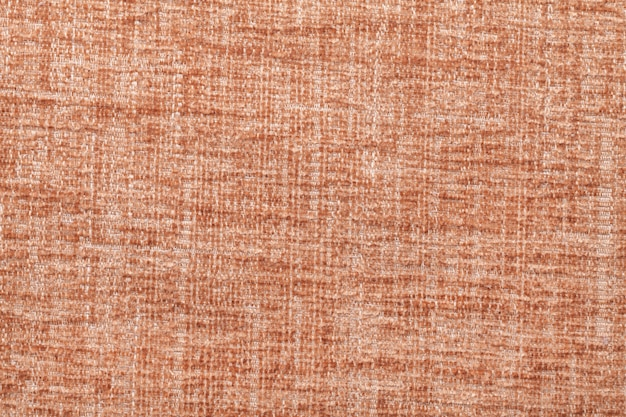Orange fluffy background of soft, fleecy cloth. texture of textile closeup.