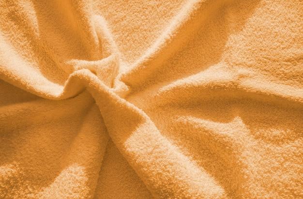 オレンジ色のふわふわテリータオル、柔らかくふわふわした生地のテクスチャの簡単な例、折り目の背景