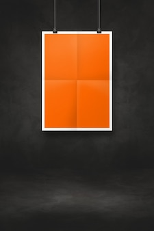 Orange folded poster hanging on a black wall with clips. blank mockup template