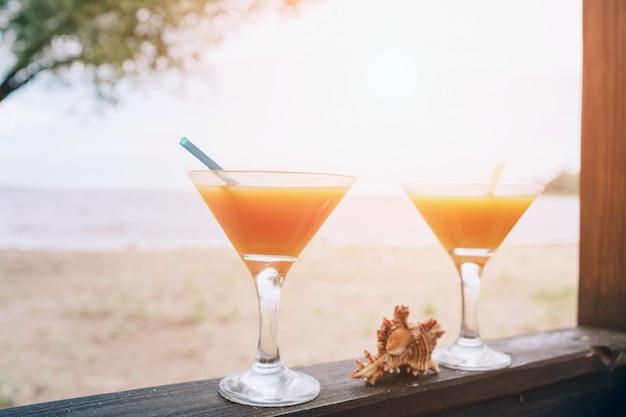 木製の端にオレンジ色の新鮮なエキゾチックなカクテル。眼鏡の間に横たわるシェル。島の生活