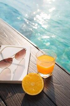 プールの近くのオレンジフレッシュジュース、本、サングラス