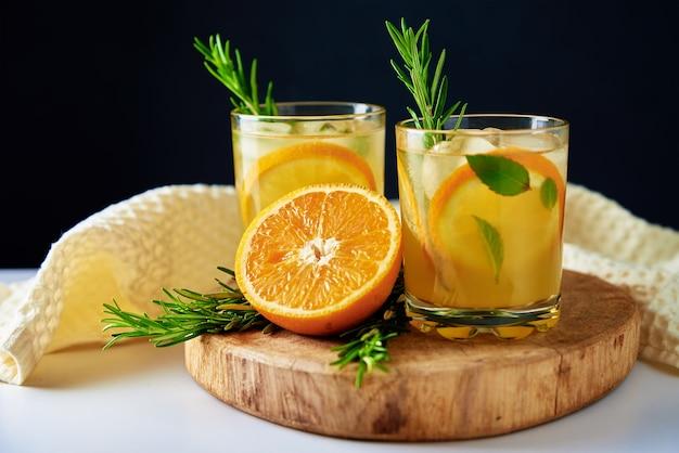 Оранжевый свежий лимонад в стекле на темном фоне
