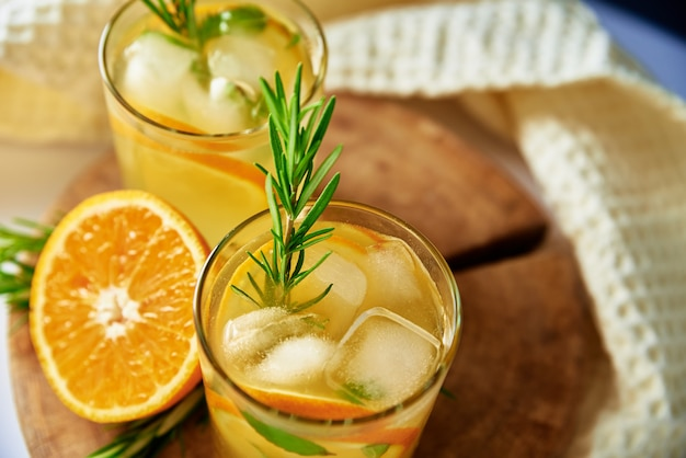 Orange fresh lemonadewith rosemaru in glass on table