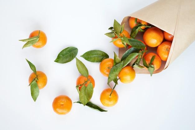 紙袋に緑の葉とオレンジの新鮮なみかん