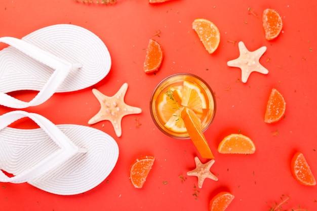 Апельсиновый фруктовый коктейль, вода для детоксикации возле белых шлепанцев.