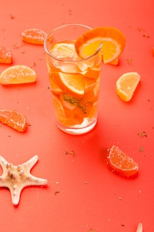 Апельсиновый фруктовый коктейль, детокс-вода на оранжевом фоне
