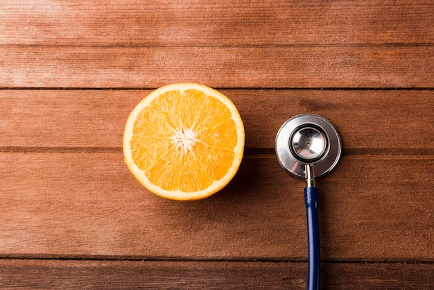 Orange fruit and doctor stethoscope on wooden table