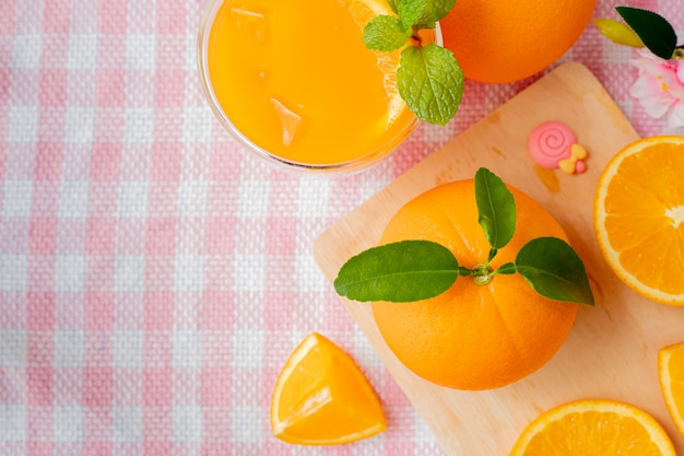 Orange fruit and glass of cold orange juice on pink tablecloth.