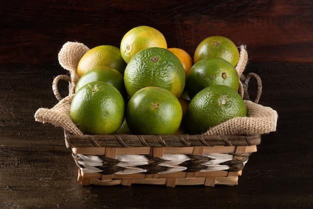 Апельсин в корзине тропических фруктов