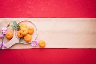 オレンジ色の果実、赤いテクスチャ背景上のテキストのコピースペースとピンクの桜。