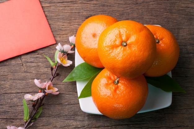 Orange fruit and red envelope on wood background