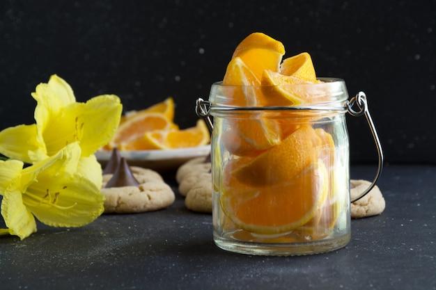 Orange fruit slices in glass jar on dark background healthy living concept
