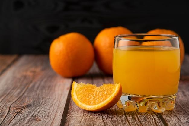 Апельсиновый фрукт со стаканом сока на деревянном столе Бесплатные Фотографии